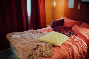 white and pink bed pillow on bed