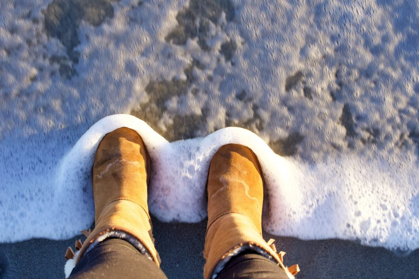 person in brown winter boots standing on snow covered ground