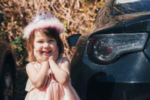 girl in pink dress sitting on black car