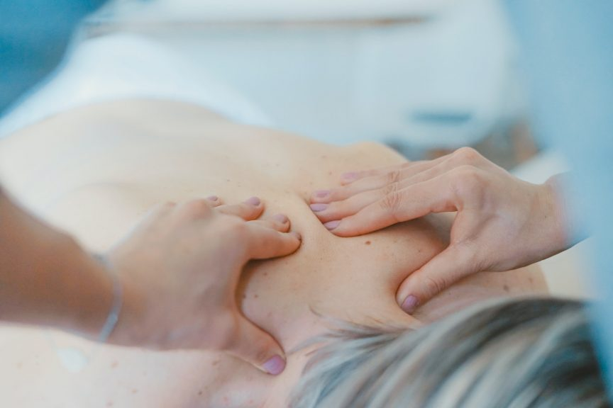 person massaging the back of a woman