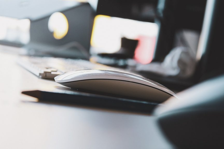 black and yellow computer mouse on white desk